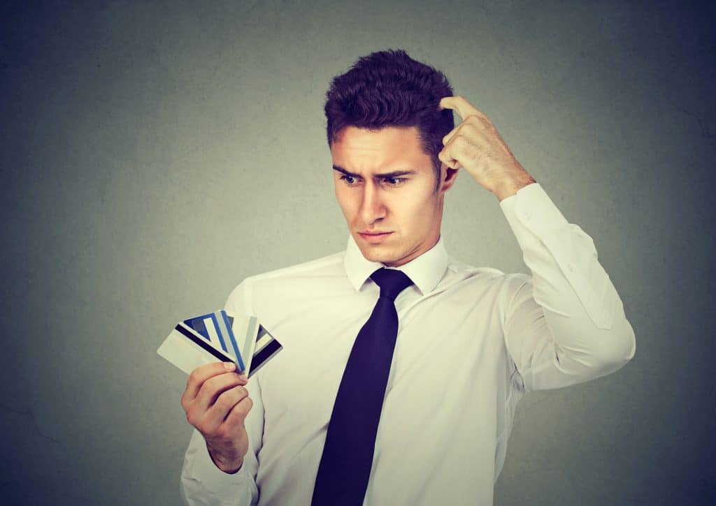 Confused man looking at many credit cards uncertain which one to choose isolated on gray background