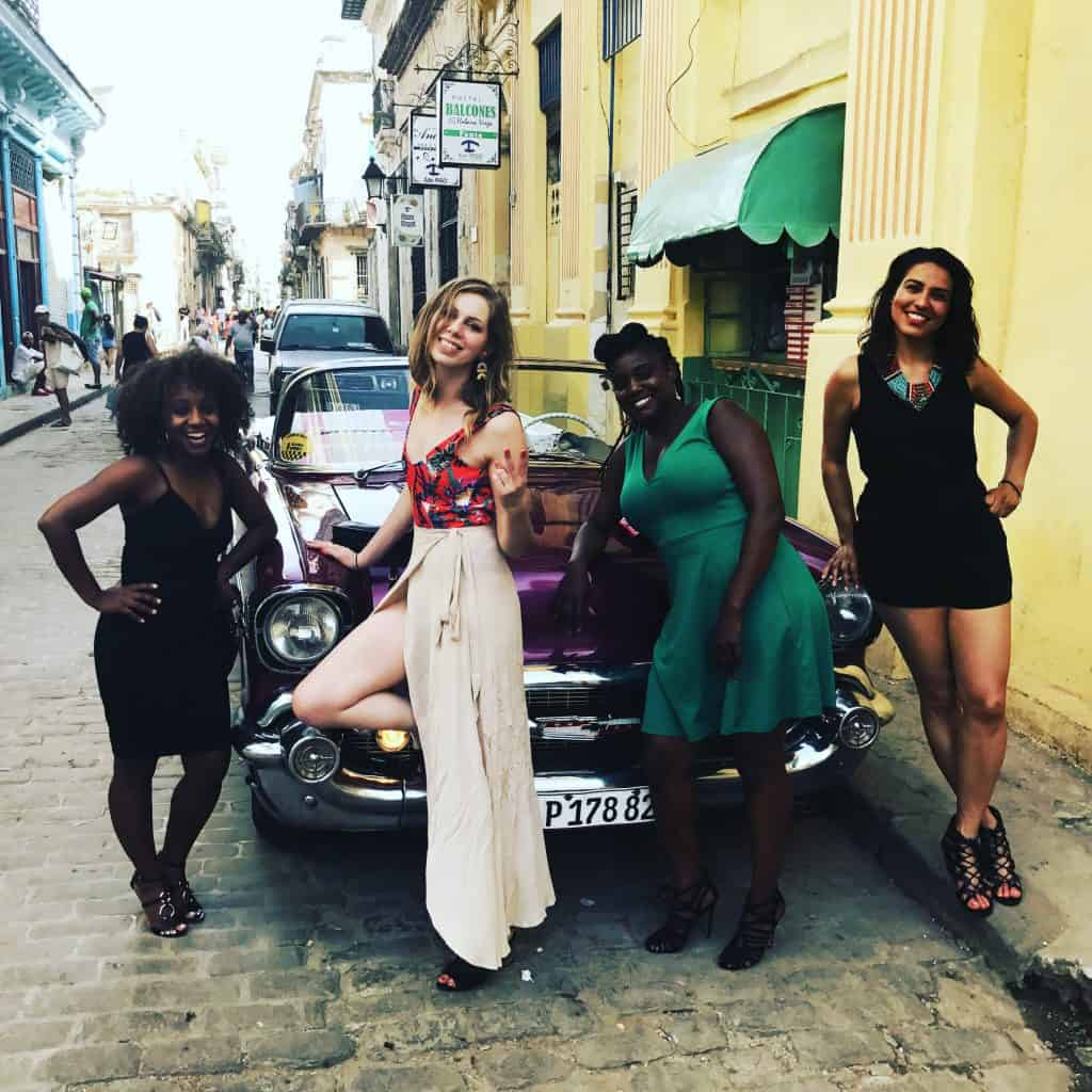 Women in front of Classic car in Cuba